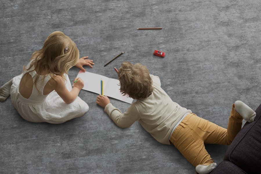 Two children on floor drawing on paper